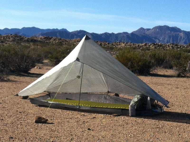 The poncho has been set up as the groundsheet under the zPacks Hexamid shelter.