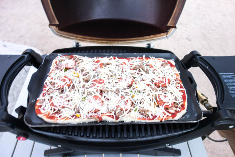 Place the Pizza in the Baby Q. Because of the pan, the temperature will drop to about 300-350 F (depending where you are camping). Bake it for about 15 minutes, or until the cheese starts to bubble. Since you made the dough very thin, it is now perfect.